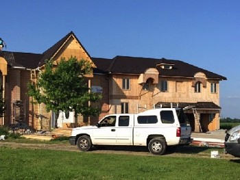 Pre-construction home with construction crew installing custom windows & doors in Mississauga.