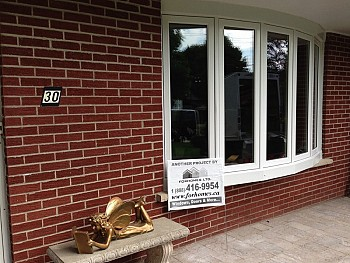 Custom white aluminum bow window installation on red brick home in Mississauga.