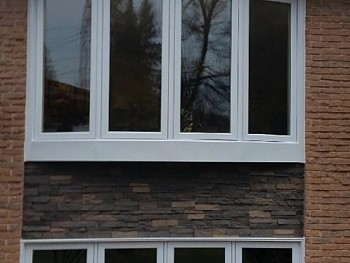 White tilt-and-turn style bow window installed over modern stonework.