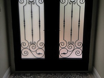 Almost Black two panel fiberglass entry door with custom wrought iron 3/4 glass