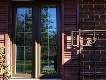Contemporary vinyl windows with brown pain on the outside and false shutters/ grilles