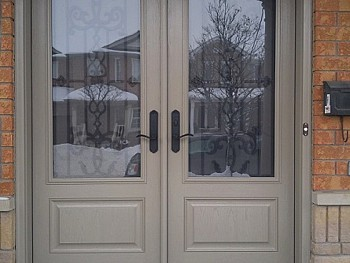 Double steel doors with wrought iron glass inserts and EMTEK lock